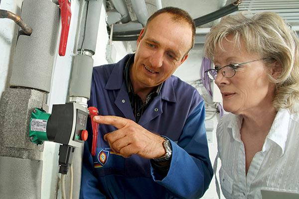 Fachhandwerker erklärt Kundin neue Heizungspumpe